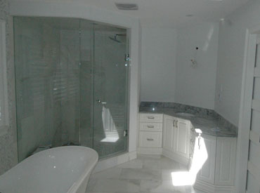 Custom bathroom vanity painted in white and glass shower enclosure